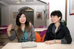 Twee Aziatische meisjes die in koffie zitten Stock Afbeeldingen