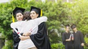 Twee Aziatische studentes met de graduatietoga's en Th van de hoedenomhelzing stock afbeeldingen