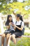 Twee Aziatische van de het gezichtsholding van het tienergeluk smartphone in hand tal stock afbeelding
