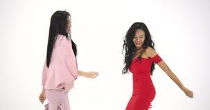Twee Aziatische vrouwen die pret hebben die als gek bij witte achtergrond dansen Mensen met partij, viering, plezier en nieuw stock videobeelden