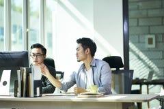 Twee Aziatische zakenlieden die in bureau samenwerken stock afbeeldingen