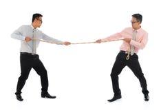 Twee Aziatische zakenlieden die een kabel trekken Royalty-vrije Stock Afbeeldingen