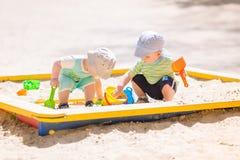 Twee babyjongens die met zand spelen Stock Foto