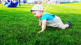 Twee babys die op het heldergroene gras op een warme de zomerdag kruipen stock videobeelden