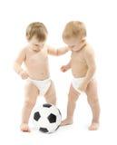 Twee babys die voetbalbal over wit spelen Royalty-vrije Stock Foto's