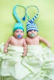 Twee babys van tweelingenbroers weared in hoeden Stock Afbeelding