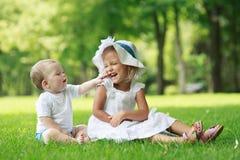 Twee babys zitten op het gras royalty-vrije stock afbeeldingen