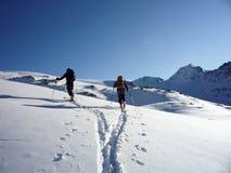 Twee backcountry skiërs op een reis in de Oostenrijkse Alpen en het aanbrengen van nieuwe sporen op hun manier aan de top Stock Foto