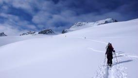 Twee backcountry skiërs op een reis in de Oostenrijkse Alpen en het aanbrengen van nieuwe sporen op hun manier aan de top Stock Afbeelding