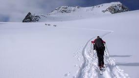 Twee backcountry skiërs op een reis in de Oostenrijkse Alpen en het aanbrengen van nieuwe sporen op hun manier aan de top Stock Fotografie