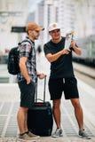 Twee backpackers bekijken een kaart bij station reis concept stock afbeelding