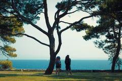 Twee backpackers dichtbij pijnboom-boom die van mening over het overzees genieten - Dalmatië, Kroatië Stock Afbeeldingen