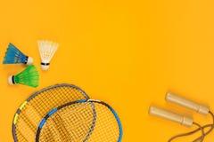 Twee badmintonrackets en twee shuttles naast een springtouw op gele achtergrond stock afbeelding