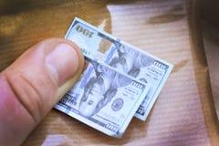 Twee bankbiljetten in het bedrag van 100 in miniatuur, tegen de achtergrond van een document verpakker, een grap, een teleurstell Stock Foto