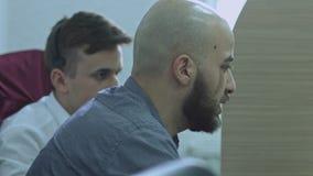 Twee bedrijfsarbeiders die in bureau bespreken en computermonitor bekijken Één mens die op computer richten stock videobeelden