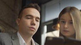 Twee bedrijfscollega's in formele slijtage die en hun smartphone in koffie zitten gebruiken tijdens vergadering stock videobeelden