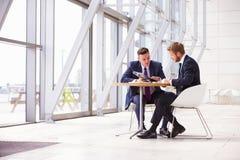 Twee bedrijfscollega's op vergadering in modern bureaubinnenland royalty-vrije stock foto