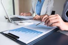 Twee bedrijfsleidersvrouwen die de grafieken en de grafieken bespreken die de resultaten tonen royalty-vrije stock afbeeldingen