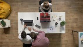 Twee bedrijfsmannen die over laptop spreken wanneer vrouw die en bij lijst in modern bureau werken zitten, topshot, het werkconce stock footage
