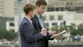 Twee bedrijfsmensen bespreken iets terwijl het lopen op een straat in Coronado stock video