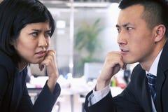 Twee Bedrijfsmensen die bij elkaar over een lijst staren Stock Foto