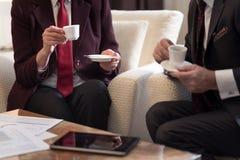 Twee bedrijfsmensen die de koppen van koffie houden Stock Foto