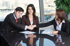 Twee bedrijfsmensen die een handdruk over een overeenkomst maken Royalty-vrije Stock Foto's
