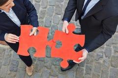 Twee bedrijfsmensen die figuurzaag oplossen royalty-vrije stock afbeeldingen