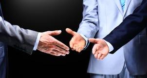 Twee bedrijfsmensen die handen schudden aan hun leider Stock Foto's