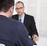 Twee bedrijfsmensen die in het bureau zitten: vergadering of baangesprek Royalty-vrije Stock Foto's
