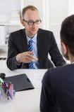 Twee bedrijfsmensen die in het bureau zitten: vergadering of baangesprek Stock Foto's