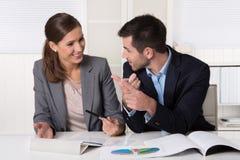 Twee bedrijfsmensen die in het en bureau zitten die spreken analyseren Stock Fotografie