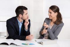 Twee bedrijfsmensen die in het en bureau zitten die spreken analyseren Royalty-vrije Stock Fotografie