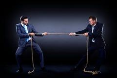 Twee bedrijfsmensen die kabel in de concurrentie trekken Stock Foto's