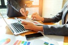 Twee bedrijfsmensen die op een grafiek richten om gegevens te analyseren Stock Afbeelding