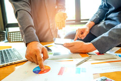 Twee bedrijfsmensen die op een grafiek richten om gegevens te analyseren Royalty-vrije Stock Afbeeldingen