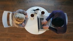 Twee bedrijfsmensen in een restaurant die, man die laptop, vrouw het drinken koffie met behulp van werken Stock Foto