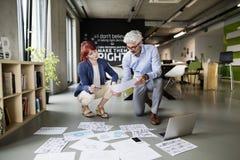 Twee bedrijfsmensen in het bureau die een project samen raadplegen stock afbeeldingen