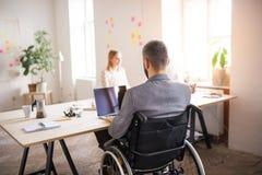 Twee bedrijfsmensen met rolstoel in het bureau Stock Afbeelding