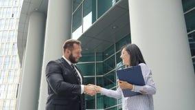 Twee bedrijfsmensenman en van de vrouw het schudden overhandigt in openlucht dichtbij commercieel centrum stock videobeelden