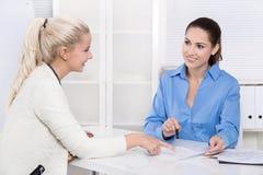 Twee bedrijfsvrouw bij bureau - toepassing of gesprek die - spreken Stock Fotografie