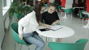 Twee bedrijfsvrouwen in de cafetaria om bedrijfskwesties te bespreken stock footage
