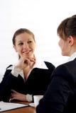 Twee bedrijfsvrouwen die bij een lijst zitten Stock Afbeeldingen