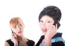 Twee bedrijfsvrouwen die door celtelefoons spreken Royalty-vrije Stock Afbeeldingen