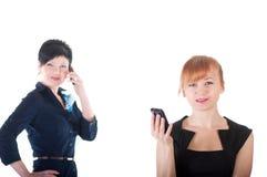 Twee bedrijfsvrouwen die door celtelefoons spreken Stock Foto's