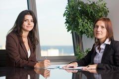 Twee bedrijfsvrouwen die een overeenkomst beëindigen Stock Foto's