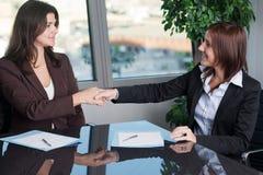 Twee bedrijfsvrouwen die een overeenkomst beëindigen Stock Afbeeldingen