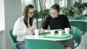Twee bedrijfsvrouwen die koffie drinken en bedrijfsvragen in de cafetaria bespreken stock videobeelden