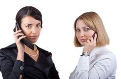 Twee bedrijfsvrouwen die op mobiele telefoon spreken Stock Afbeelding