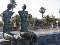 Twee beeldhouwwerken van een man en vrouwen zonder wapens zaten langs een straat van Barcelona in Spanje Royalty-vrije Stock Foto's